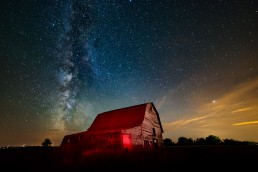 Barn lit with red headlamp, Milky Way, green airglow and light clouds lit with light pollution