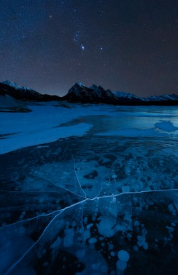 Methane bubbles and cracks shaped like a shattered skull in Abraham lake with orion in the sky