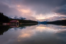 Pink clouds opening to reveal mountain ranges at Malign Lake, the boat launch reflects in the still lake