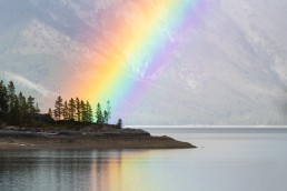 Bright rainbow over an outlet at Lake Minnewanka shot with a telephoto lens