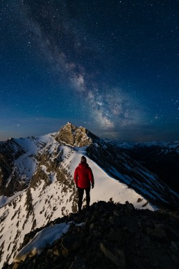 Solo woman hiker in red jacket stands on ridge in front of snowy mountain with milky way in the sky