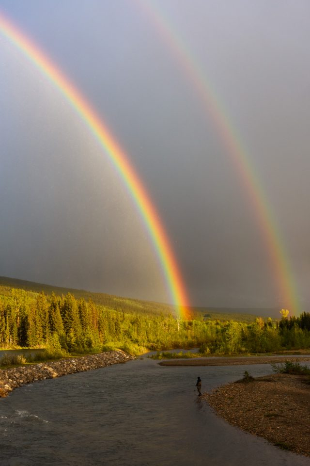 A fishman stands in the belly river with two bright rainbows forming above in a dark stormy sky
