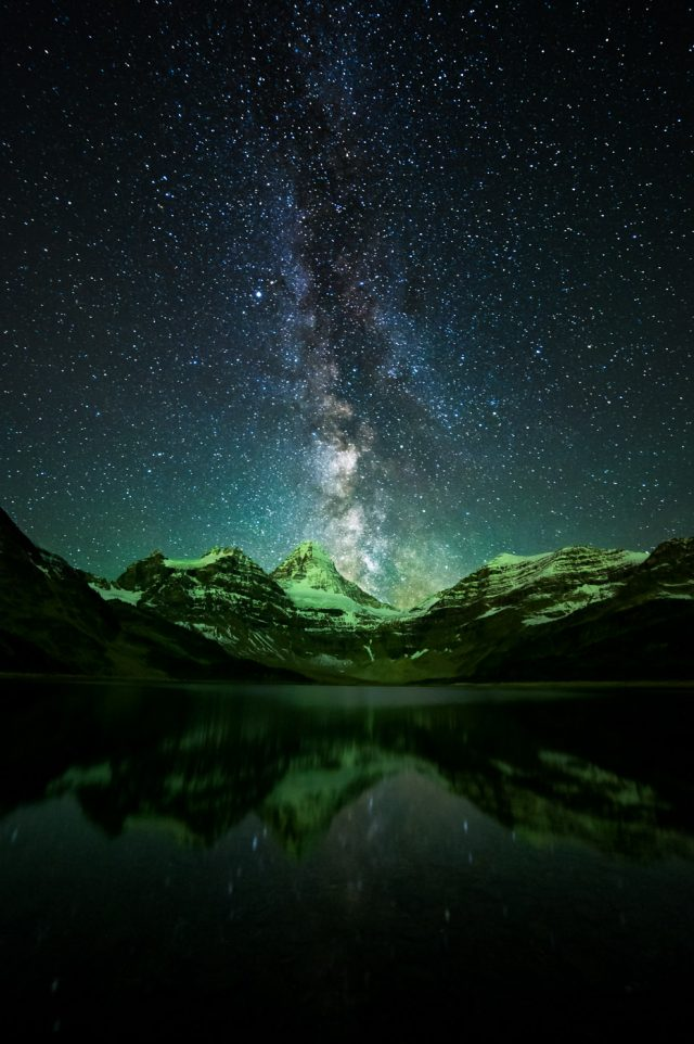 Milky Way next to Mount Assiniboine with aurora borealis lighting up the mountains with green light
