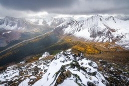 Dramatic skies and larches over a valley in Highwood Pass