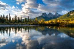 Rain drops rippling in Policemans Creek as sunlight hits fall colours and the three sisters in Canmore