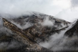 Mist and clouds flow through a mountain with ridges in Waterton